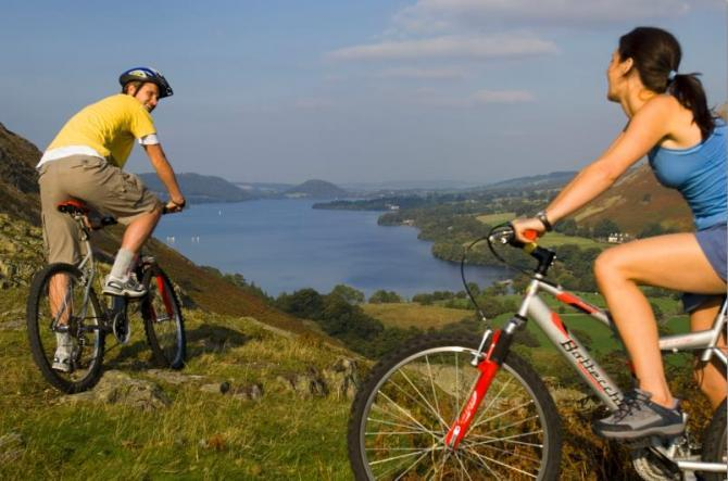 Cyclists on a hilltop near Martindale overlooking Ullswater - Britain On View