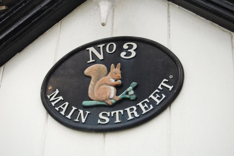 Decorative sign over the old original front Porch incorporating the native Lakes red squirrel. - No. 3 Main Street