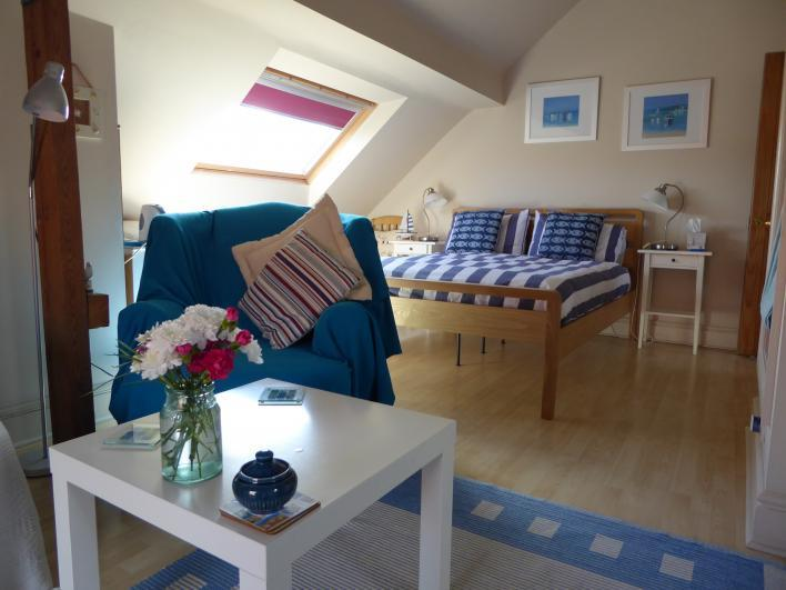 Lymehurst Bed and Breakfast Seaside themed guestroom with kingsize & single bed and cosy seating area.