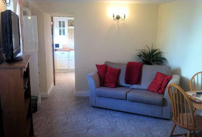 Harry's Cottage Harry's Cottage, Peel - Sleeps 2/4. Stylish living room with sofa, dining table and Freeview TV.