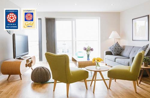 Snaptrip - Last minute cottages - Luxury Newquay Views S25792 - The lounge with floor to ceiling windows that open to a private balcony with stunning sea views.