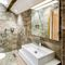 The Great Barn, Ullswater, The Lake District First floor: Cockpit - en-suite natural stone bathroom with bath and separate monsoon and raindrop shower