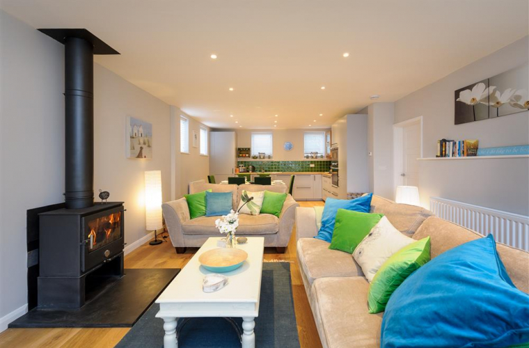 Open plan living room and kitchen with a wood burner