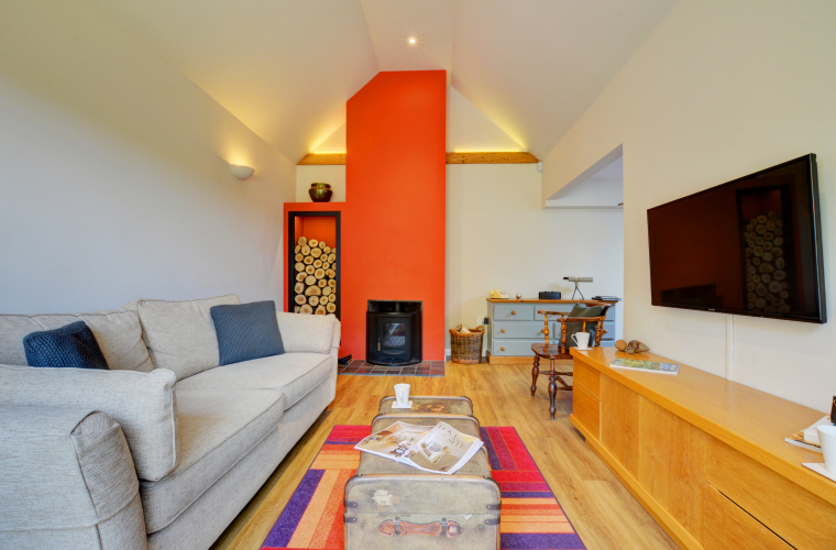 Bright living room with an orange chimney breast.