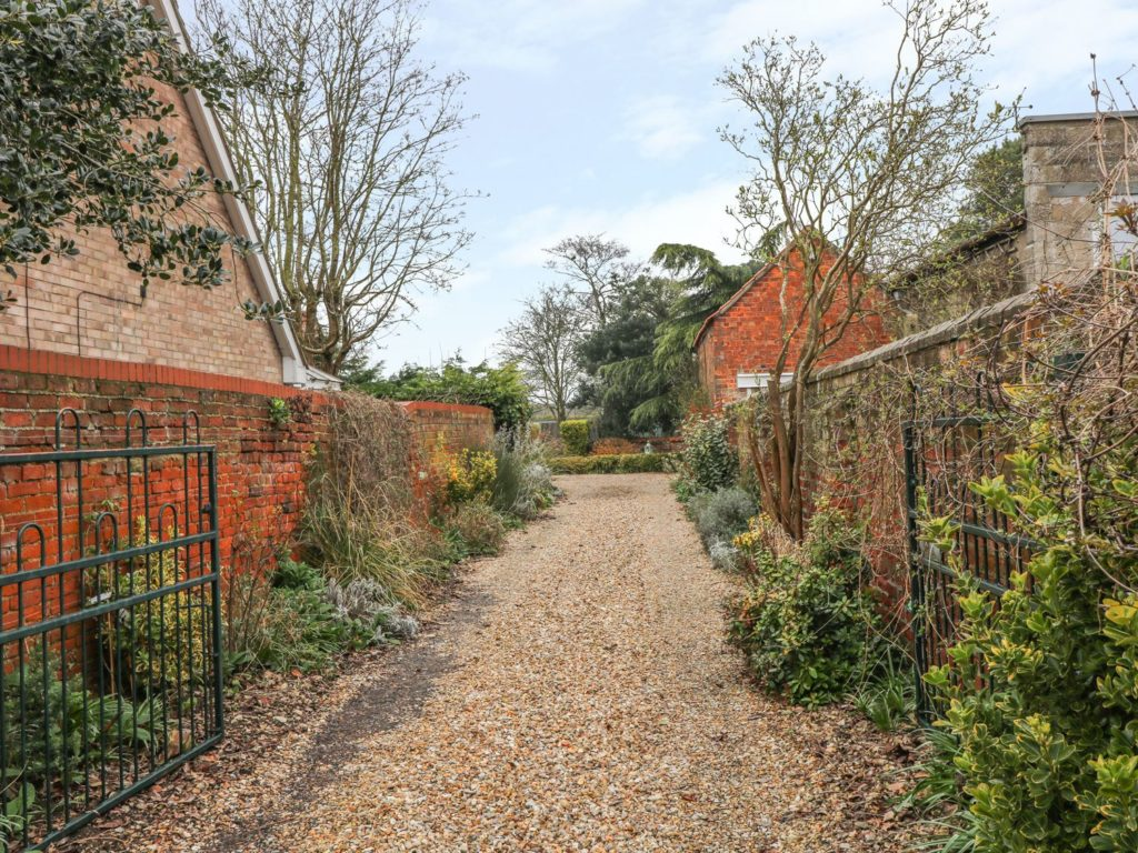A gravel drive entrance with red brick walls and lots of plants.
