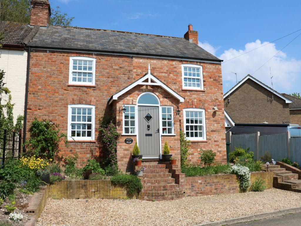 A semi-detached brick cottage with steps up to the front door and well kept flower beds.