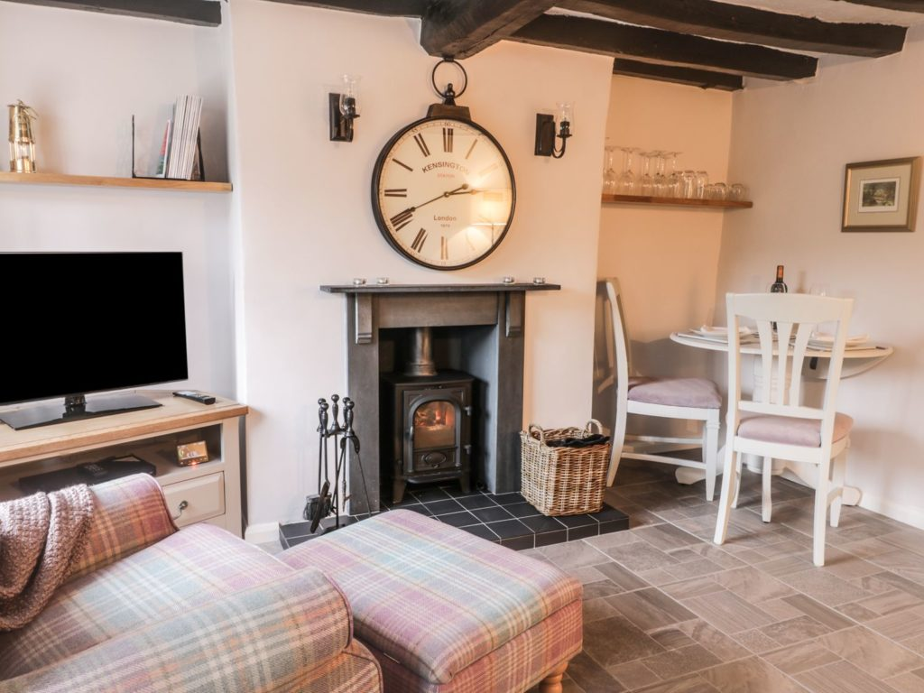 A cosy living room with an oversized clock on the wall above a wood burner. It also has a flat screen TV, armchair and table for two.