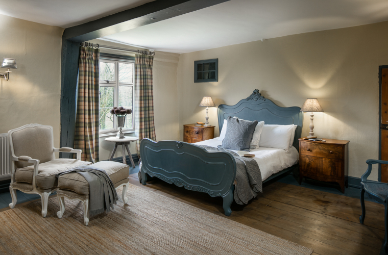 A cosy double bedroom with wooden floors and a solid blue bed frame.