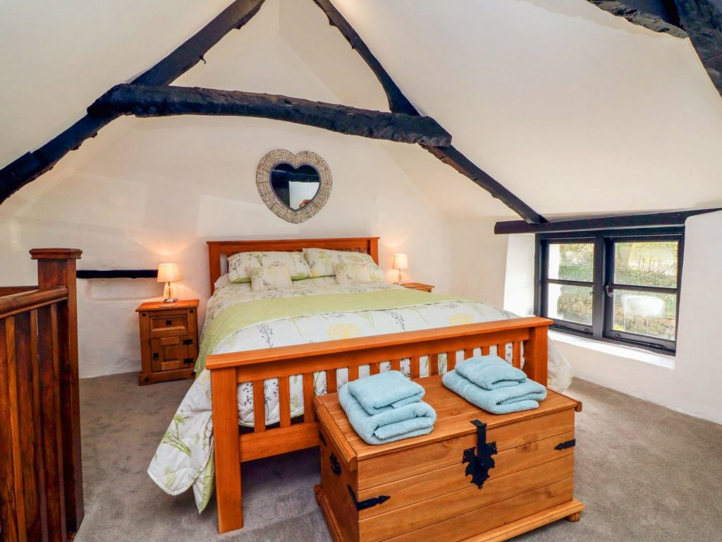 Room with a double bed, exposed beams and a heart shaped mirror