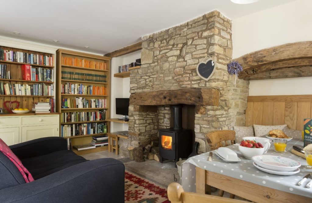 Cosy living room with a bookshelf, wood burning stove, and wooden table