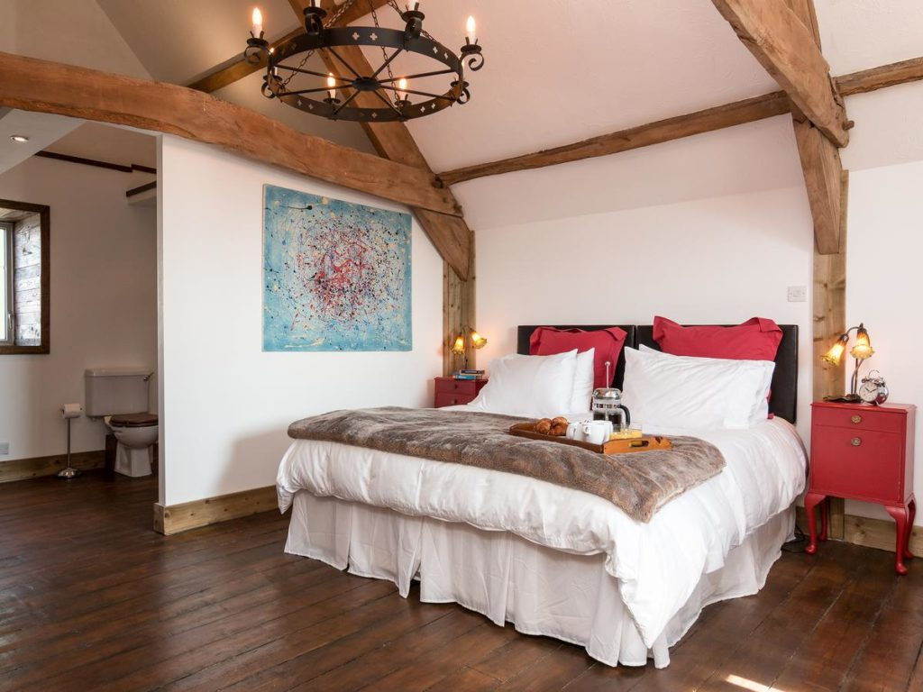 Room with a double bed and exposed beams