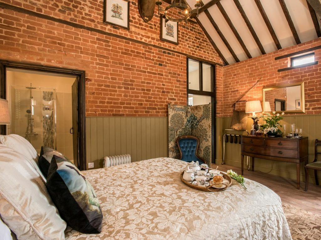 Room with exposed brick and beams. It has a double bed and is elegantly decorated.
