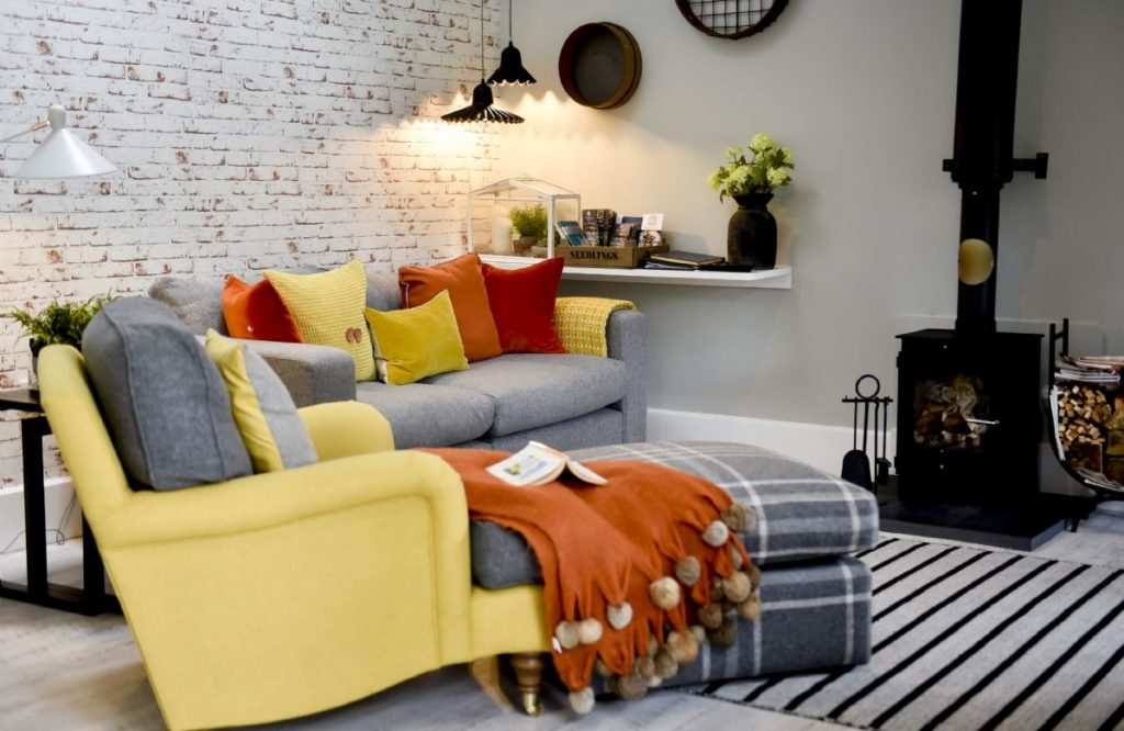 A living room with a sofa, colourful pillows and a wood burner